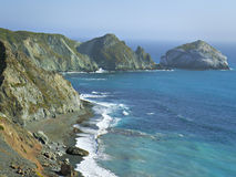 California Coast from Highway One. Rugged cliffs overlooking seashore with blue sea and crashing waves stock photography