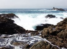 California Coastal Rocks and Cliffs, Rippling Water Surface - Road Trip down Highway 1. Waves of the Pacific ocean crashing against the rocks of the Californian royalty free stock photography