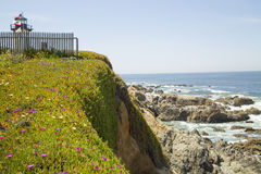 California coastline with lighthouse flags flowers and a picket Stock Photos