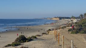 California Coastline. Surfers, lifeguards, tourists, families all come together to relish a beautiful day and enjoy the rocky coast stock image