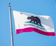 California Flag. California historic flag in the wind against blue sky showing bear and star of the flag royalty free stock image