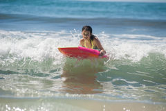 California girls grow up in the ocean. Girl child floating on green ocean as she rides the boogie board Stock Image