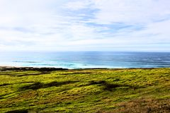California highway 1 one Pacific ocean. California blue sky on the coast near big sur green grass royalty free stock image