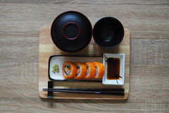 California maki roll in square plate Japanese style served with shoyu sauce and wasabi. On table wood Stock Image