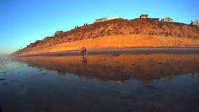 California Moonlight Beach Coastal Cliffs. West coast beach scene with low tide coastal cliffs and 2 people walking Moonlight Beach Encinitas San Diego stock video