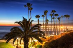 California Oceanside pier with palm trees view. California Oceanside pier over the ocean with palm trees and beach, travel destination Royalty Free Stock Photo