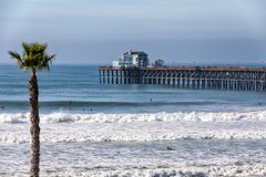California Oceanside pier with palm trees view. California Oceanside pier over the ocean with paln trees and beach, travel destination Stock Photos