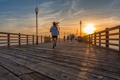 California Oceanside pier at sunset. A girl running on Oceanside pier at sunset, California Stock Image