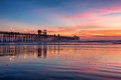 California Oceanside pier at sunset. California Oceanside pier over the ocean at sunset with beach, travel destination Royalty Free Stock Images