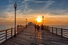California Oceanside pier at sunset. People walking on Oceanside pier at sunse, California Royalty Free Stock Images