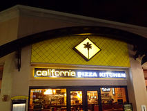 California Pizza Kitchen Logo glows above of food establishment Stock Images