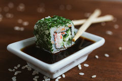 California roll in greens in soy sauce with chopsticks. On dark background Stock Image