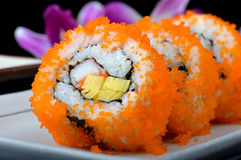 California roll or Japanese sushi roll. California roll or Japanese sushi roll with flying fish roe or shrimp roe cut and set on white plate in black background stock photography