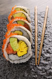 California roll sushi chopsticks on black plate Royalty Free Stock Photo