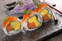 California roll sushi with chopsticks on black plate Royalty Free Stock Photos