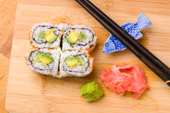 California rolls appetizer with rice avocado with chopsticks. Sushi is often prepared with raw seafood, but some common varieties of sushi use cooked royalty free stock photography