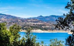 California`s Lake Cachuma with San Rafael Mountains. Lake Cachuma in California with lush greenery and the San Rafael Mountains in the distance Stock Photos