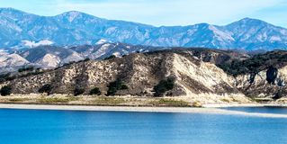 California`s Lake Cachuma with San Rafael Mountains. Lake Cachuma in California near the Los Padres National Forest with the San Rafael Mountains in the distance Royalty Free Stock Images