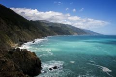 California Seascape on Highway 1 with Sunlight on Turquoise Ocean. Sun lights up ocean in turquoise colors along the cliffs and mountains on California Highway 1 stock photography