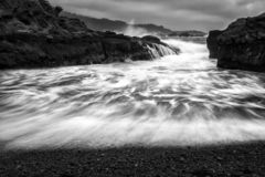 California Seascape in Motion in Black and White with Surge and Spray. California seascape in motion with surf surging onto beach in dramatic black and white royalty free stock photo