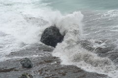 California surf crashing against boulder Royalty Free Stock Photos