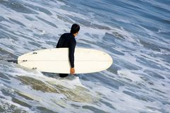 California Surfer. Surfer going into the surf with long board stock image