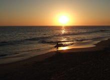 California surfer sunset. The silhouette of a California surfer walking along Laguna Beach at sunset stock photos