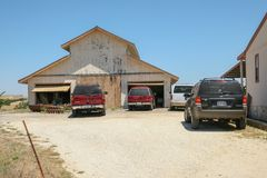 Vehicles parked outside a warehouse on a California ranch. stock photography