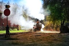 California. USA. October 2012. An ancient train moves along the rails releasing smoke in the sun royalty free stock images