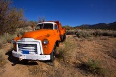 California vintage truck somewhere in desert. California vintage orange old truck somewhere abandoned in desert Royalty Free Stock Images