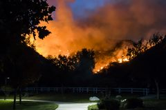 Fire Burns Hillside Behind Neighborhood Park at Night in California Brushfire. California Woolsey fire burns in hillside behind neighborhood park at night stock photos
