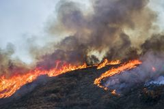 Fire Burning with Bright Orange Flames and Black Smoke on Hillside with Heart Shape in Smoke during California Fire. California Woolsey fire hillside burning stock image