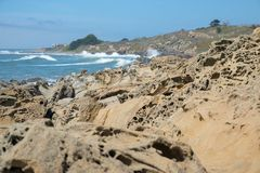 Californian shore with structured foreground. Waves at the Californian shore with an structured foreground of microcaves in the sand stock image