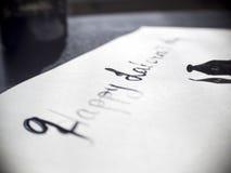 Caligrafía de trabajo feliz del día del ` s y postal lattering Visión izquierda con la pluma del calligraph Imagen de archivo