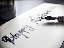 Caligrafía de trabajo feliz del día del ` s y postal lattering Visión izquierda con la pluma del calligraph Imagen de archivo libre de regalías