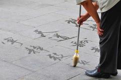 Caligrafía en la tierra, Pekín, China de la escritura del hombre fotos de archivo libres de regalías