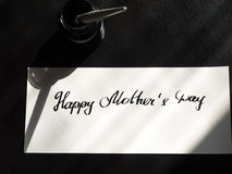 Caligrafía feliz del día del ` s de la madre y postal lattering Luz del sol de la ventana Foto de archivo