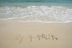 Caligrafia chinesa pelo ano novo feliz escrito na areia Fotos de Stock Royalty Free