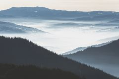 Calimani Mountains. Dorna Basin covered in low fog and the peaks of Calimani Mountains in the background Stock Photo