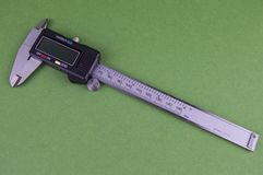 Caliper with digital screen on a green background, there is free space for filling royalty free stock photo