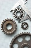 Caliper with gears and bearings. On graph paper royalty free stock photo