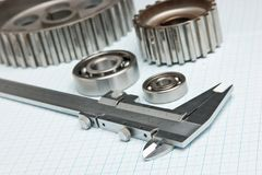 Caliper with gears and bearings. On graph paper stock photo