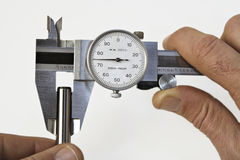 Caliper and Pin. A worker measures a pin with a dial caliper royalty free stock photography