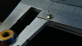 Calipers on black background. The movement of caliper. Closeup. Caliper on a black desk. Dolly shot stock footage