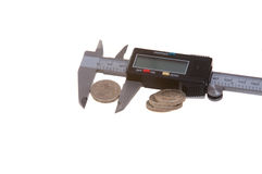 Calipers and coins. Calipers being used to measure coins Royalty Free Stock Photography