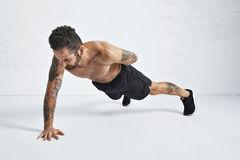 Calisthenics pushups training technique. Strong brutal tattoed and ripped male athlete shows how to do one hand push-ups, isolated on white spacious gym, top stock images