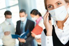 Call. Attractive woman in protective mask calling somebody in working environment royalty free stock photography