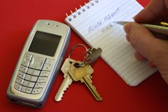 Call Agent. Hand writing on note pad with keys and mobile cell phone Royalty Free Stock Photography