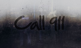 Call 911 alert message written on car or building window. Call 911 alarm message written on dark rainy window Royalty Free Stock Photography
