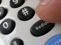 Call back. Thumb poised over telephone redial button Royalty Free Stock Photography